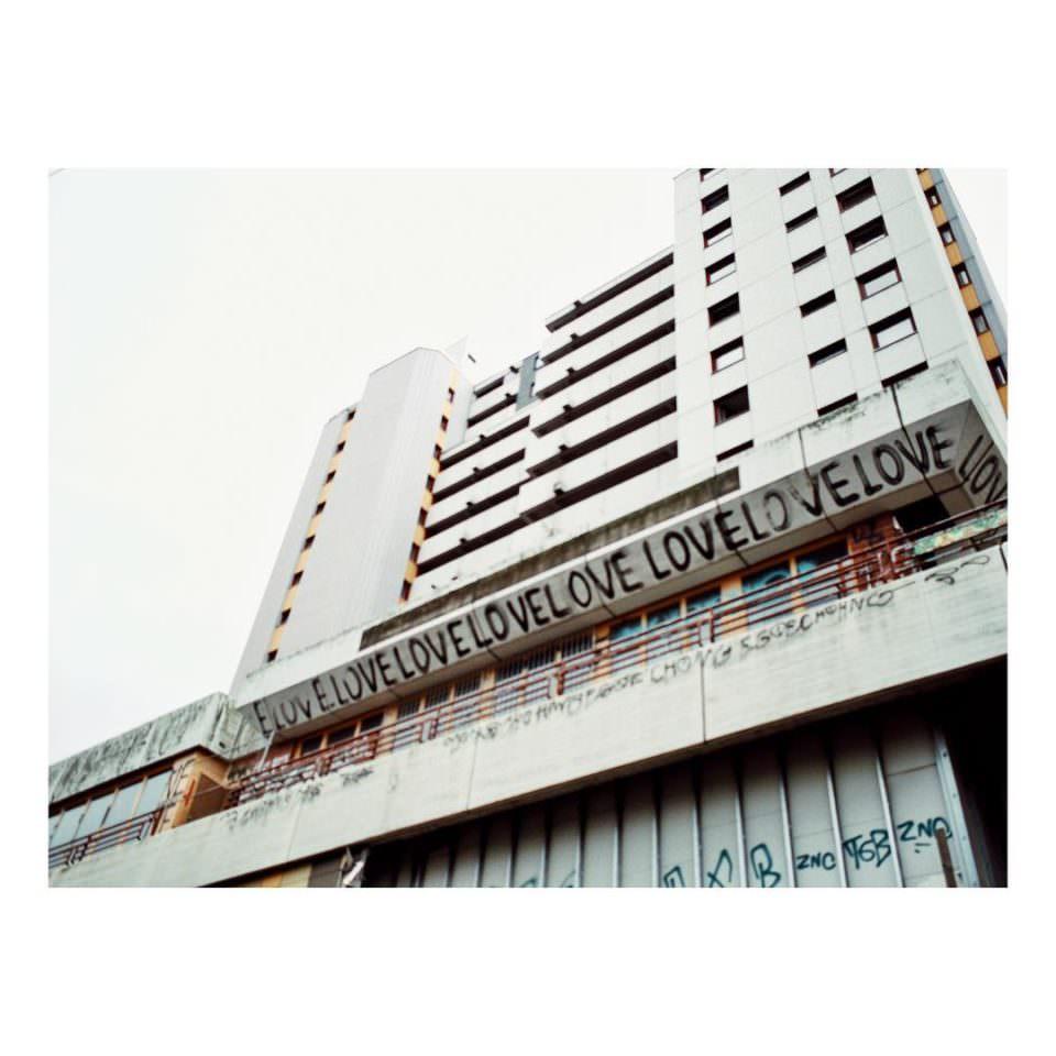 Ansicht eines Wohnblocks von unten an dem ganz oft mit Graffiti das Wort Love geschrieben steht.