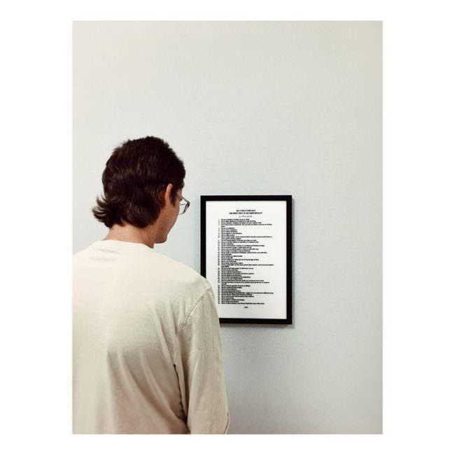 Junger Mann von hinten zu sehen, der auf ein Bild an einer Wand schaut, das nur Text zeigt.