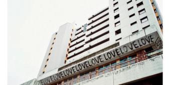 Ansicht eines Wohnblockes von unten an dem ganz oft mit Graffiti Love geschrieben steht.