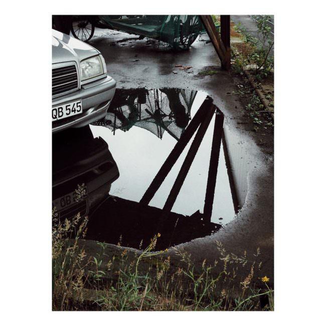 Eine Pfütze am Boden, mit einem kleinen Teil einer Mercedesschnauze und Spiegelungen von etwas außerhalb des Bildes.