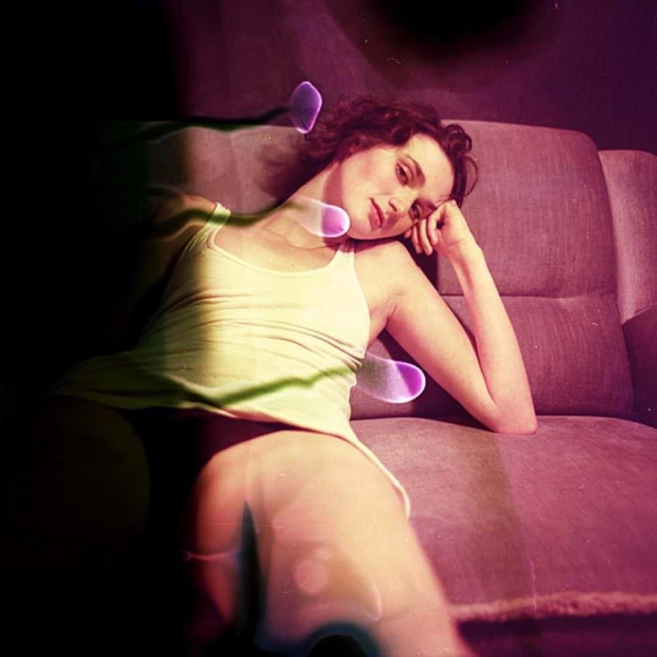 Frau leicht bekleidet sitzend auf einem Sofa mit dem Kopf auf den Arm gestützt und bunten Farbflecken im Bild.