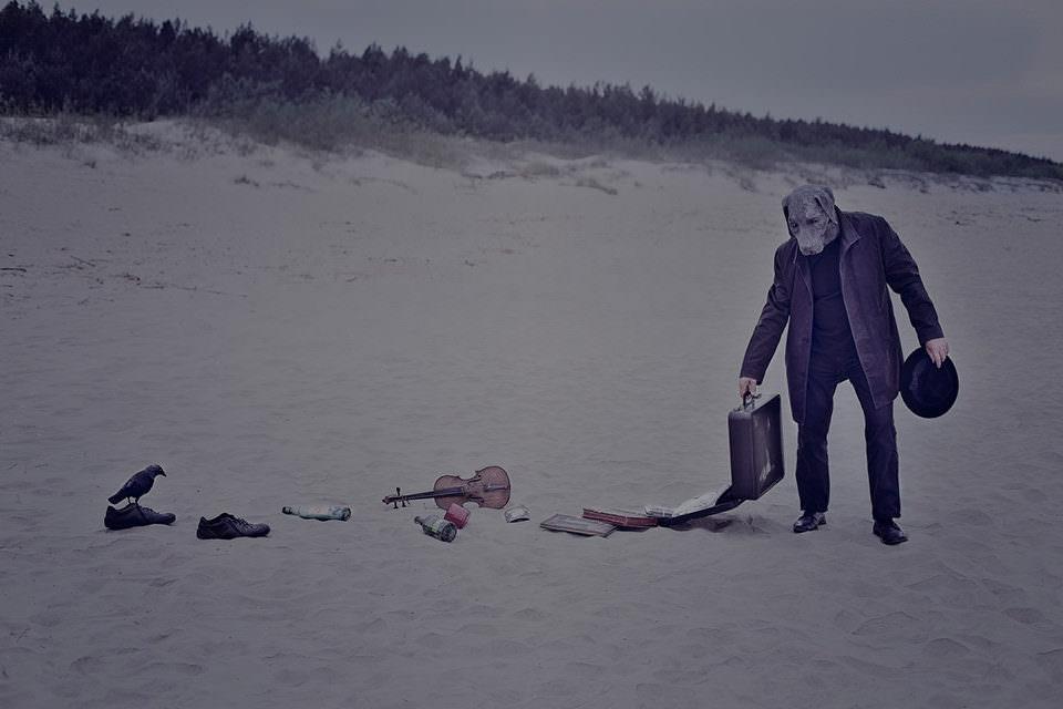Ein Hund mit offenem Koffer verliert den Inhalt im Sand