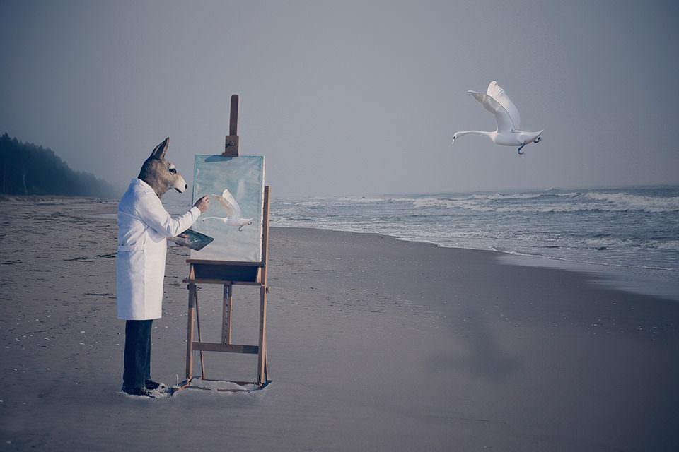 Ein Hand zeichnet mit einer Staffelei am Meer