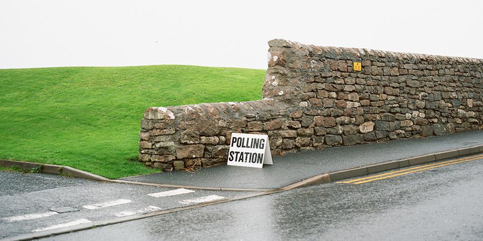 Natursteinmauer zwischen Wiese und Straße mit einem Schild auf dem Polling Station steht.