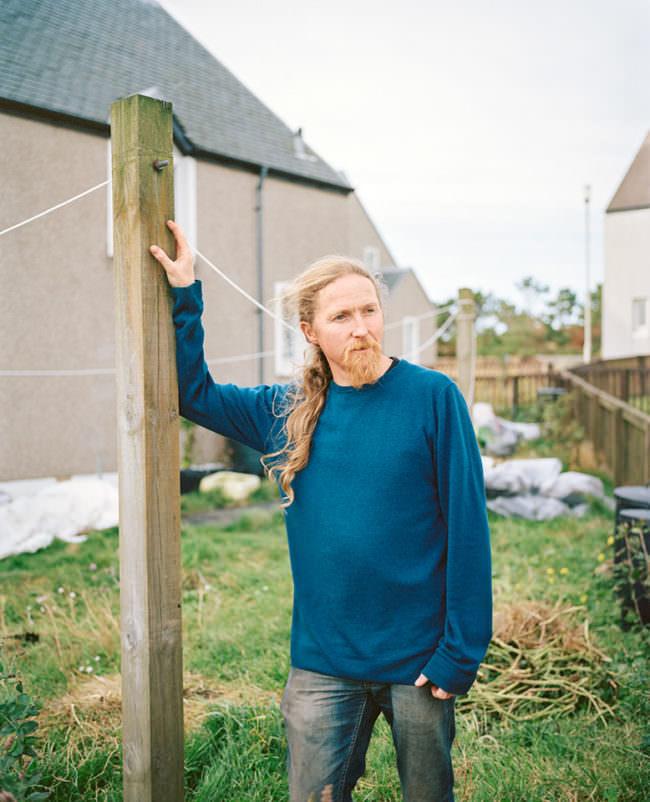 Junger Mann mit langen Haaren steht draußen an einen Pfeiler gelehnt vor einem Haus.