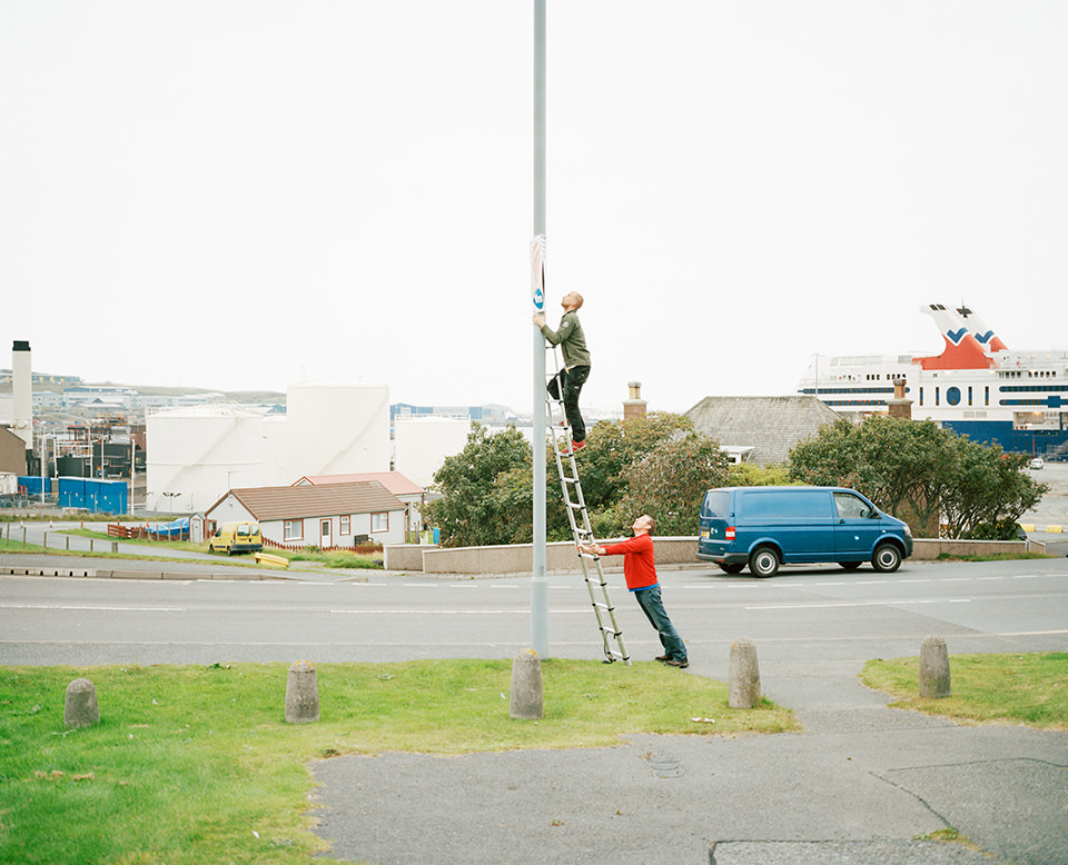 Laternenpfahl, an dem eine Leiter steht, auf der eine Person ist, während eine weitere Person unten die Leiter hält.