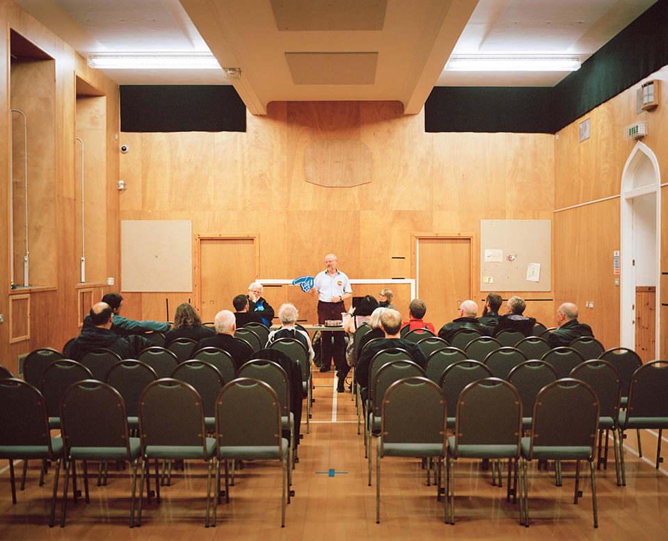 Bestuhlter Raum mit Holzvertäfelung, in dem Menschen einem Redner zuhören.
