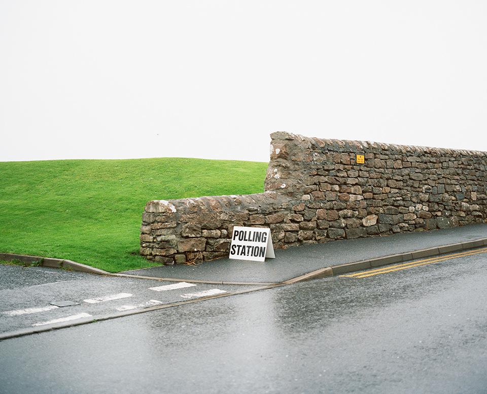 Natursteinmauer zwischen Wiese und Straße mit einem Schild, auf dem Polling Station steht.