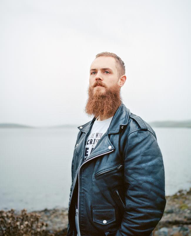 Junger Mann mit Bart und Lederjacke steht vor einer Meeresszenerie.