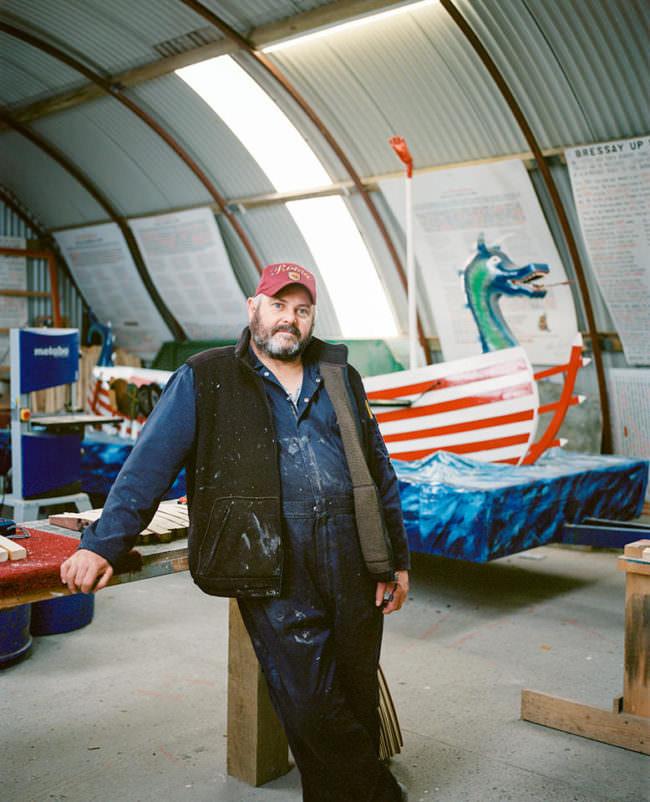 Mann mit Cap steht in einer Werkshalle vor Booten.