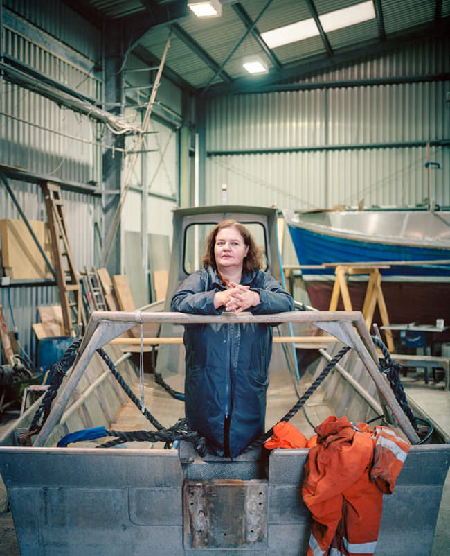 Frau steht im Blaumann in einer Werkshalle in einem Boot.
