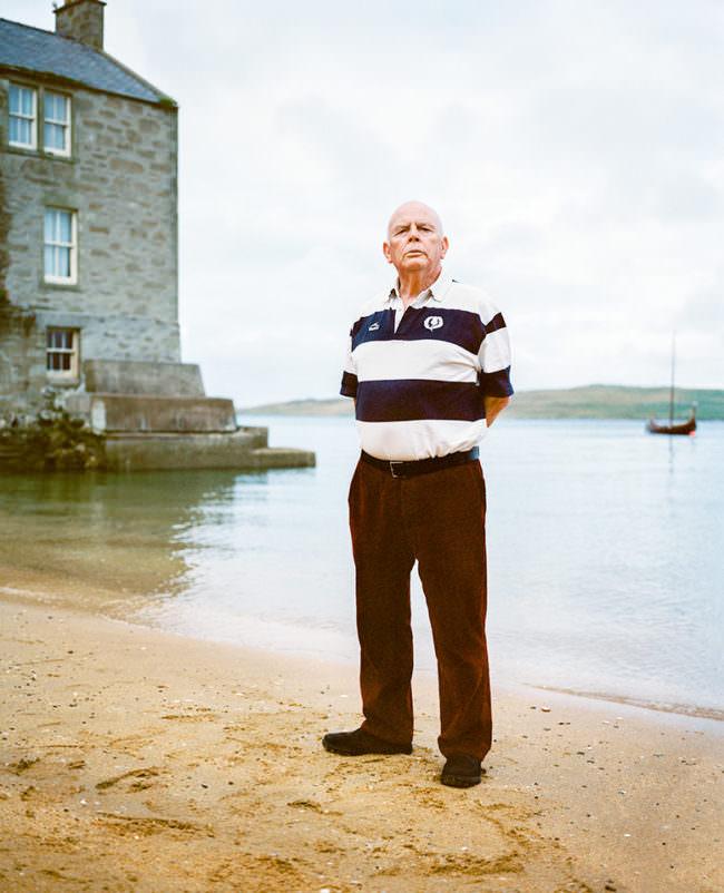Älterer Herr in gestreiftem Shirt steht am Wasser, im Hintergrund ein steinernes Haus und ein Boot.