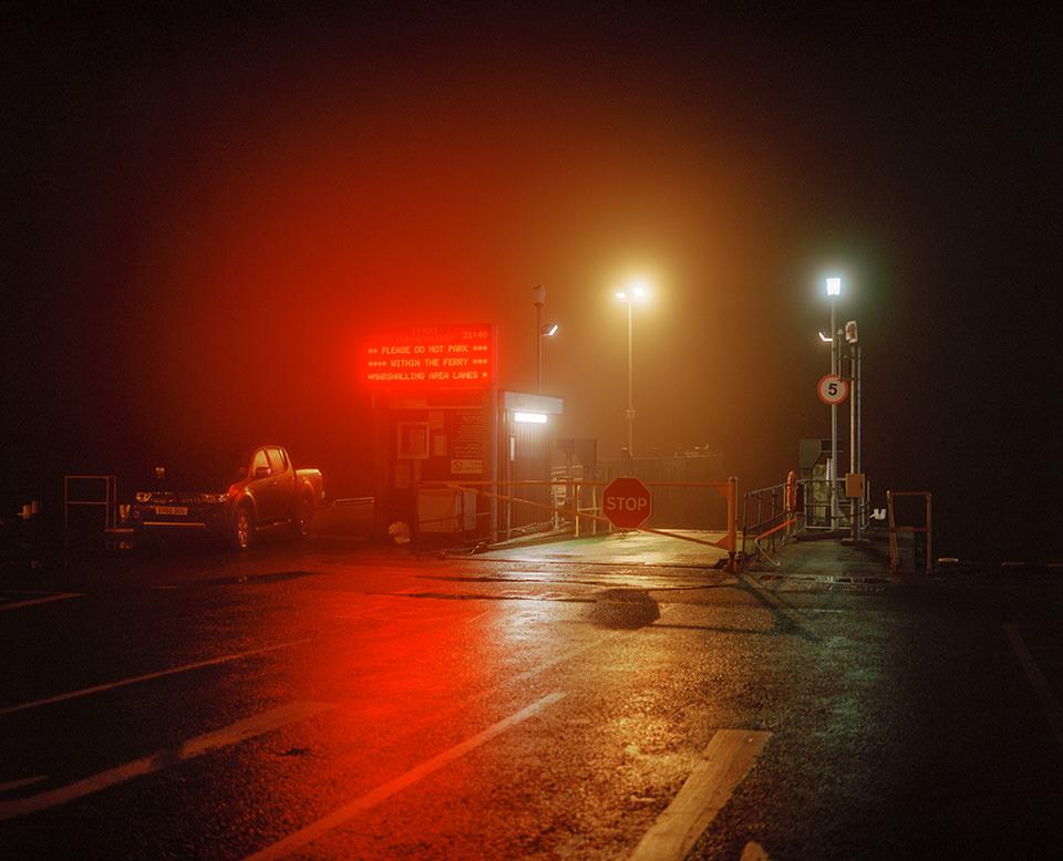 Nachtaufnahme von leuchtenden Reklamen und Lichtern an einer nassen Straße.