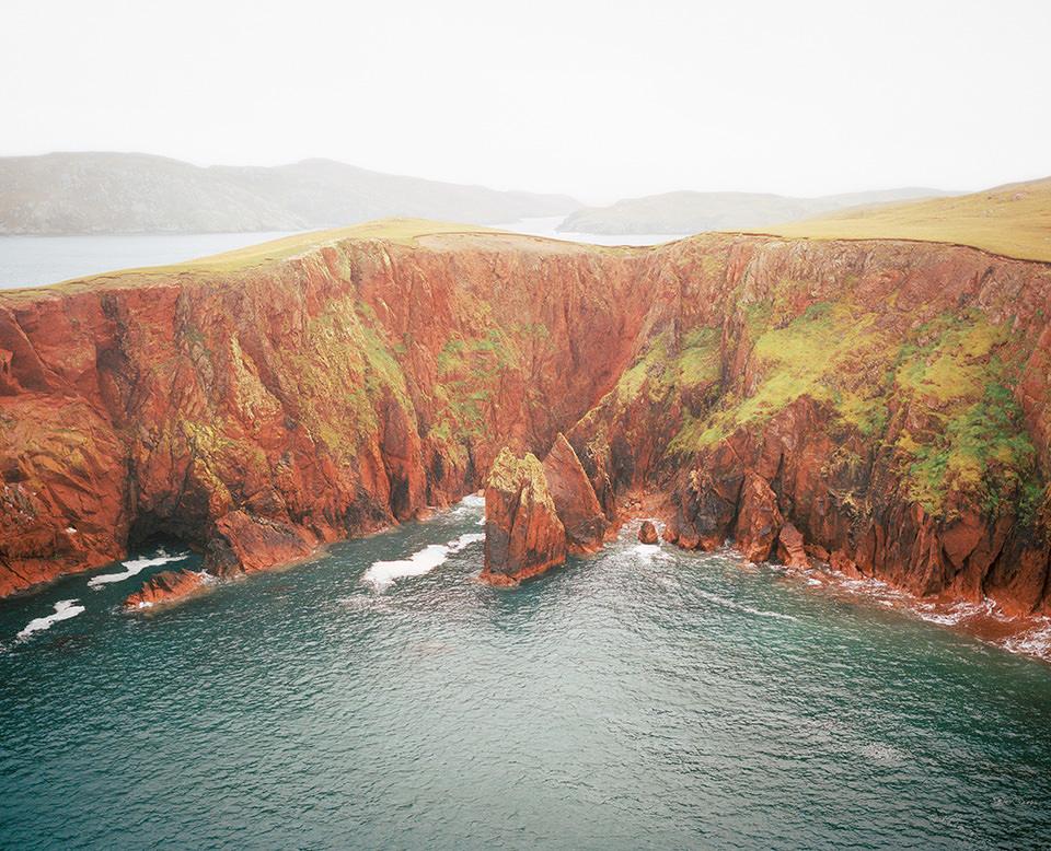 Luftblick auf Meeresbucht an gebirgiger Küstenlandschaft.