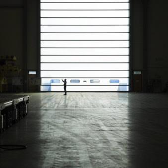 Ganz kleine Person in einer Halle vor einem riesigen Rolltor.