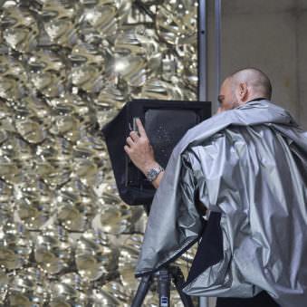 Eine glitzernde Wand vor der ein Mann mit Silberumhang und einer Großformatkamera sitzt.