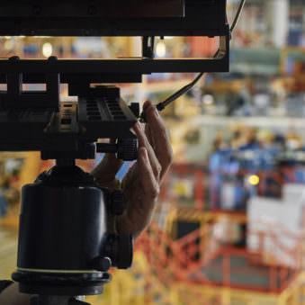 Detailaufnahme einer Hand an Einstellrädchen einer Großformatkamera.