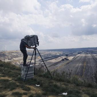 Person steht auf einer Kiste in einer Landschaft mit viel Himmel und schaut durch eine Großfomratkamera auf einem Stativ.