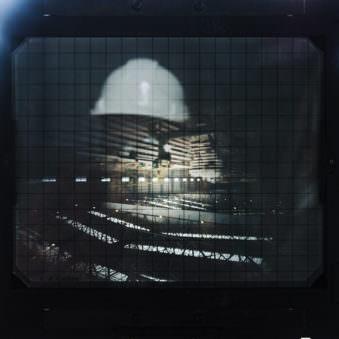 Spiegelung von etwas Schemenhaftem auf der Mattscheibe einer Großformatkamera.