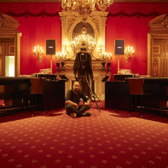 Portrait eines sitzenden jungen Mannes in einem roten, barocken Zimmer mit Großformatkamera im Bild.