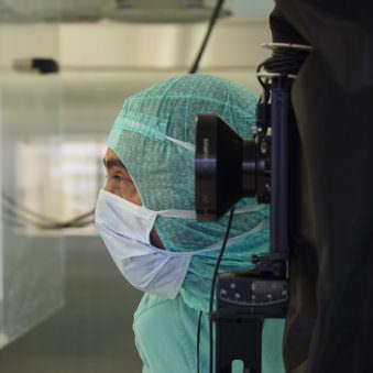 Person in grünem, medizinischen Schutzanzug und mit Mundschutz und einer angeschnitten sichtbaren Großformatkamera.