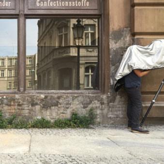 Schaufenster mit Spiegelung auf Aufschrift Confectionsstoffe, vor dem eine Person unter einem Tuch an einem Stativ steht.