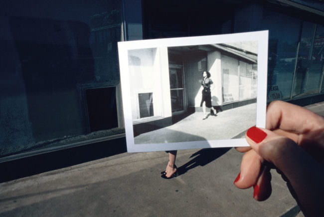 Ein Polaroid wird vor eine Straße gehalten