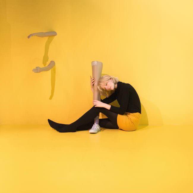 Eine Frau hält ein Bein, zwei Arme wachsen aus der Wand