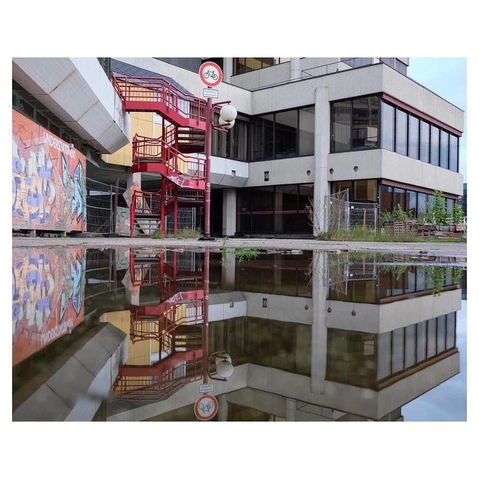 Ein Gebäude spiegelt sich in einer Pfütze