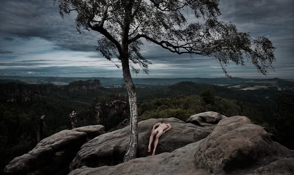 Ein Mann liegt nackt auf einem Fels