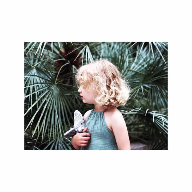 Ein Kind vor Palmblättern
