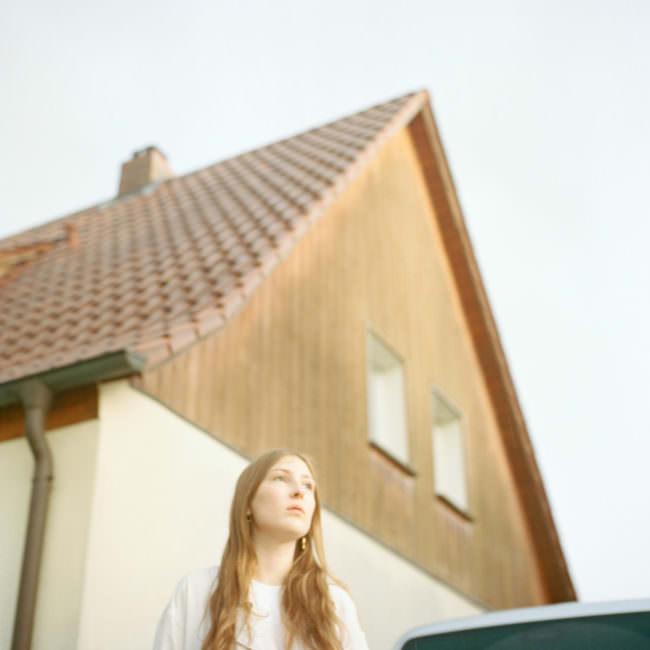 Junge Frau vor einer Hausfassade