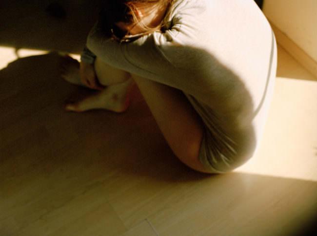 Junge Frau halb im Schatten, halb in der Sonne auf dem Boden sitzend
