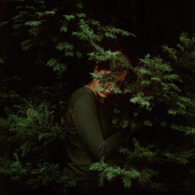 Junge Frau, in grün gekleidet, steht in einem grünen Nadelbaum
