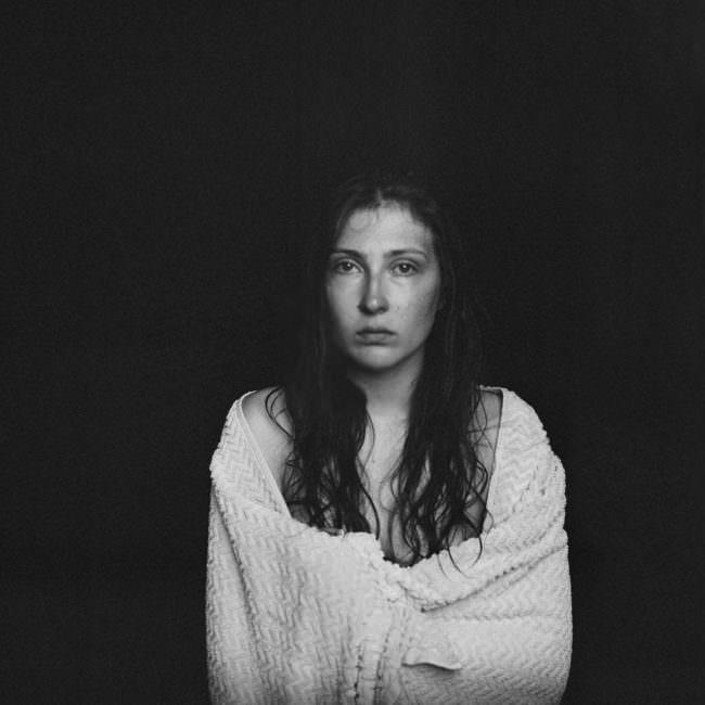 Schwarzweiß Portrait einer jungen Frau, die traurig in die Kamera blickt.