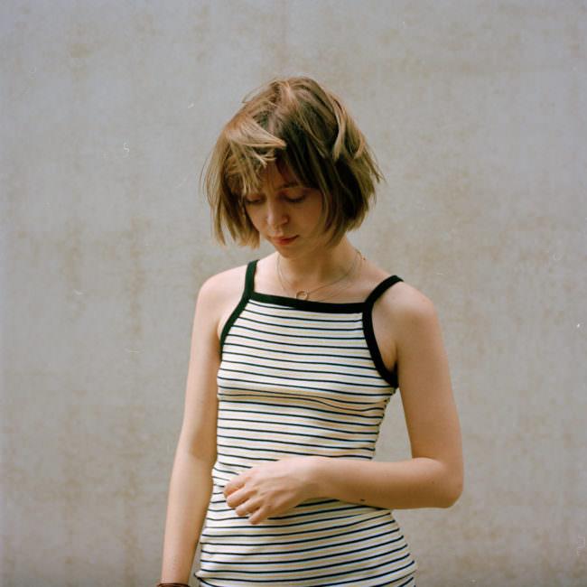 Portrait einer jungen Frau, die nach unten blickt.