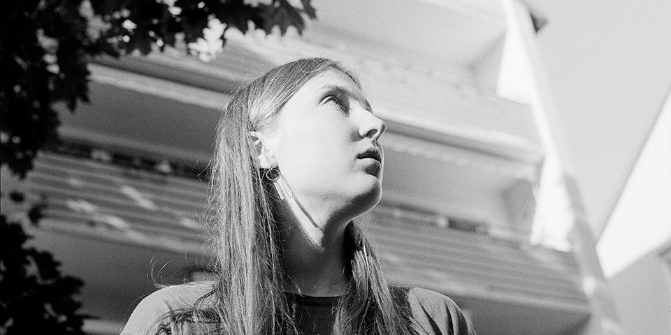 Schwarz-weiß Fotografie einer jungen Frau vor einer Hausfassade