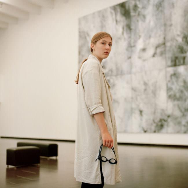 Junge Frau, in einem Museum stehend, hält eine Schwimmbrille in der Hand.