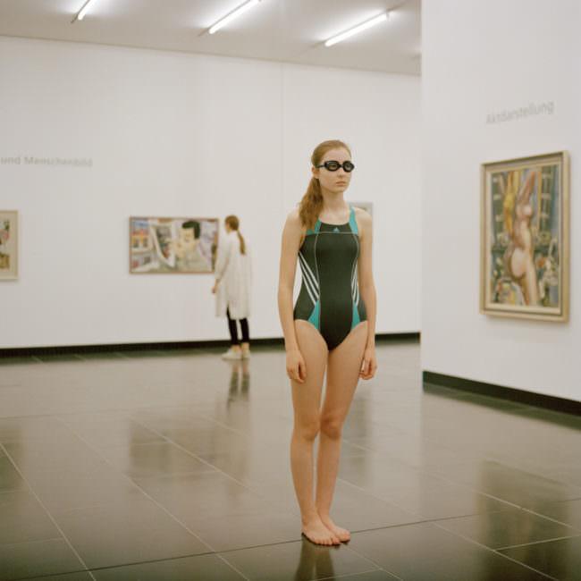 Junges Mädchen, in einem Museum stehend, mit Badeanzug und Schwimmbrille bekleidet.