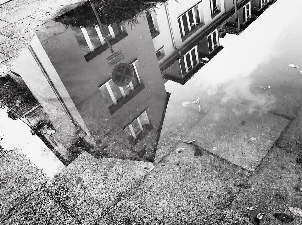 Ein Haus spiegelt sich in einer Pfütze