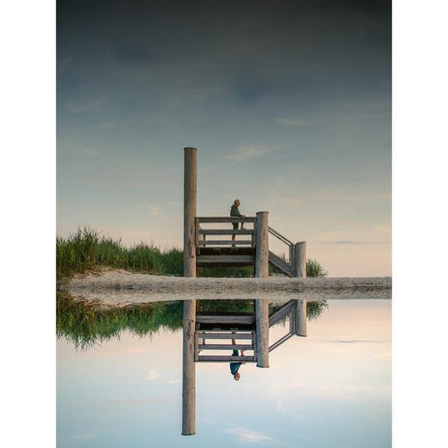 Ein Steg spiegelt sich im Wasser