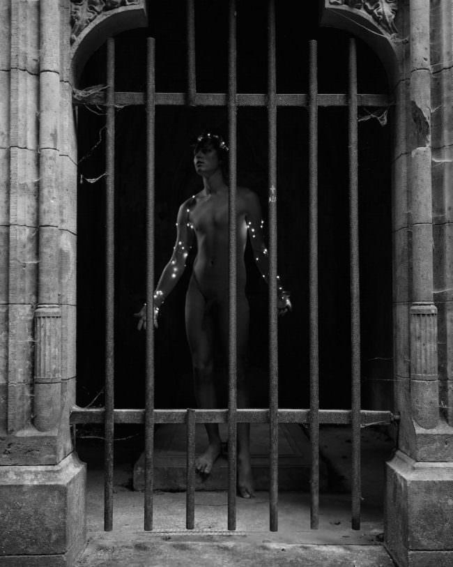 Ein mann mit Lichterkette hinter einem Gitter