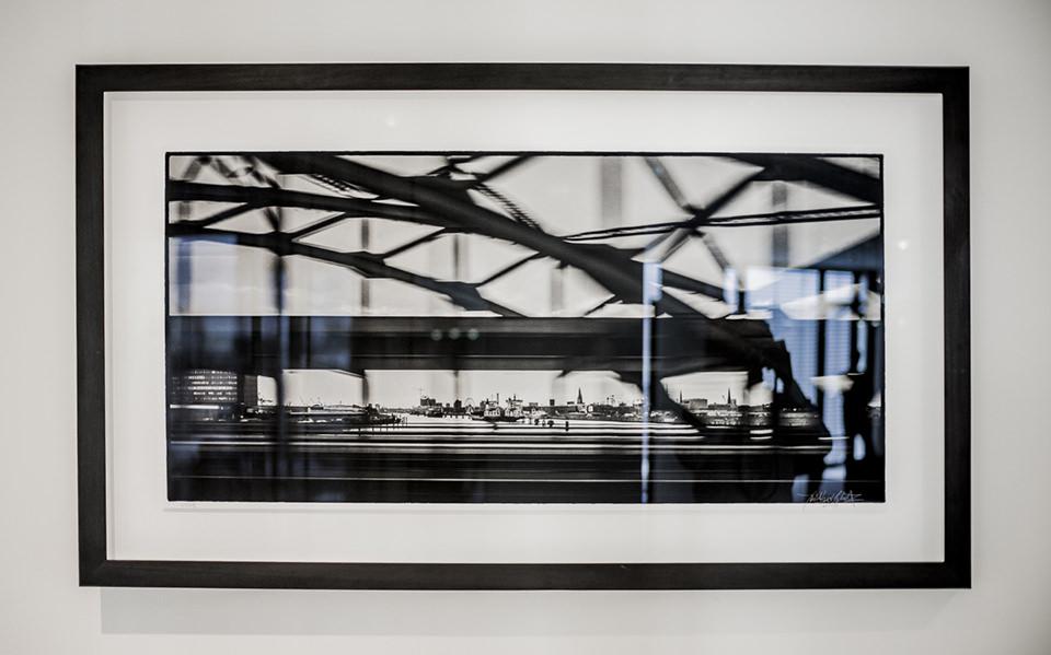 Ansicht eines gerahmten Schwarzweißfotos an einer Wand. Auf dem Bild sind verwischte Streben zu sehen.