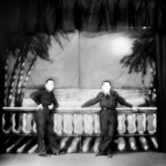 Historische Fotografie mit zwei Personen in edler Kleidung an einem Geländer lehnend, deren Gesichter unkenntlich sind.