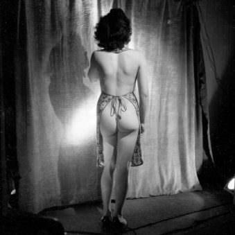 Eine Rückansicht einer beinahe nackten, jungen Frau in einem Fotostudio.