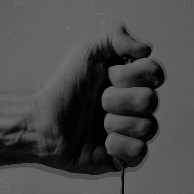 Nahaufnahme einer Hand, die einen Auslöser drückt.
