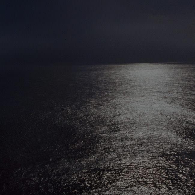 Nachtansicht auf ein leicht beschienenes Meer.