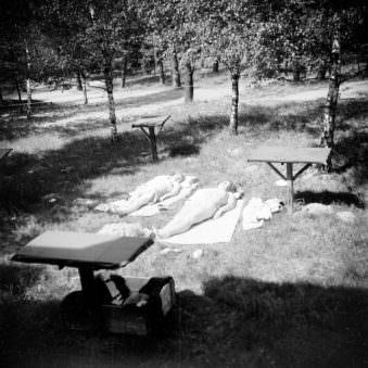 Alte Schwarzweißfotografie zweier sonnenbadender Frauen in einem Waldstück.