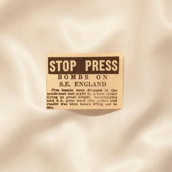 Alter Zeitungsausschnitt auf schimmerndem Stoff.