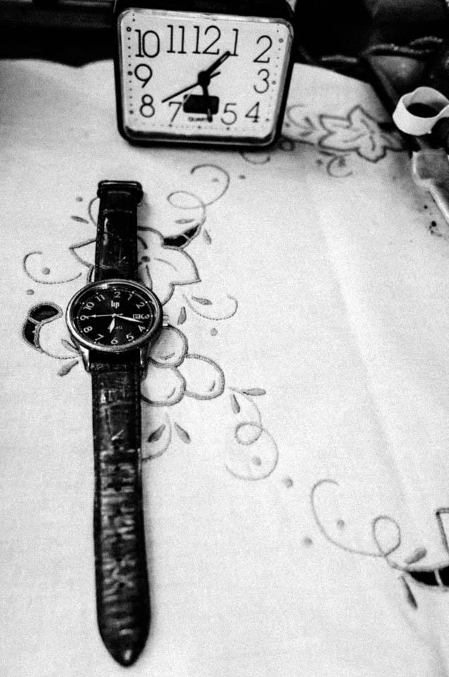 Eine Armbanduhr vor einem Wecker